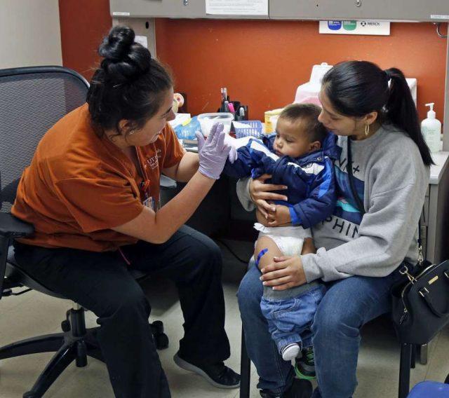 在UT-圣安东尼奥护理学院的学生Caitlin Garcia在四月份被母亲抱着他的流感疫苗后,给了亚历山大·阿尔曼扎2岁高中。 官员说,本赛季接种疫苗还不算晚。 照片:罗纳德科尔特斯,圣安东尼奥快报/ 2017罗纳德科尔特斯