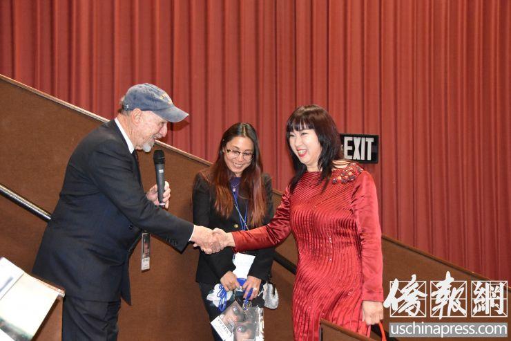 电影节主席亨特.托德(图左)与执行副主席张玲(图右)在开幕式上握手 (侨报记者陈琳摄)